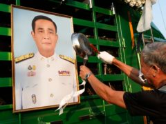 A pro-democracy protester bangs pots to make noises in front of a picture of Prime Minister Prayuth Chan-ocha (Sakchai Lalit/AP)