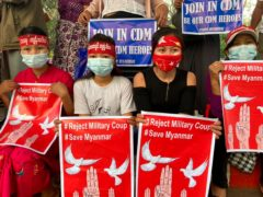 """Anti-coup protesters hold posters that read """"#Reject Military Coup #Save Myanmar"""" as they gather in Yangon on Monday. The country's military junta has threatened """"loss of life"""" if the protests continue (AP)"""