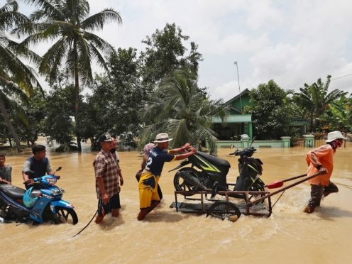 People push belongings through a flooded area in Indonesia (Achmad Ibrahim/AP)
