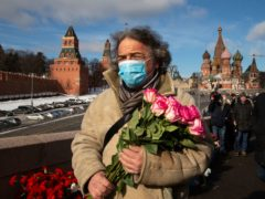 A man walks to lay flowers near where Russian opposition leader Boris Nemtsov was gunned down, in Moscow (AP/Alexander Zemlianichenko)