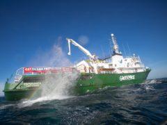 A boulder falls into the English channel from Greenpeace vessel Esperanza (Suzanne Plunkett /Greenpeace/PA)