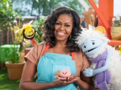 Michelle Obama with Busy, a bee puppet, left, Mochi, a pink round puppet, and Waffles, a furry puppet (Adam Rose/Netflix via AP)