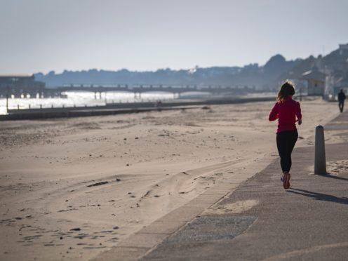 A jogger runs along Bournemouth beach in Dorset (PA)