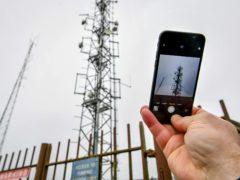 A mobile phone next to a telecom mast (Ben Birchall/PA)