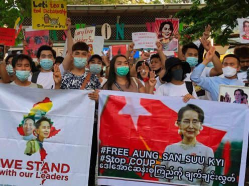 Migrant workers from Myanmar flash the three-finger protest gesture while they hold banners with images of deposed Myanmar leader Aung San Suu Kyi before participating in a march by Thai pro-democracy activists in Bangkok on Sunday (Fu Ting/AP)