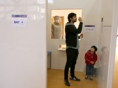Quroum Beg, with his son Hadi, takes a Covid-19 asymptomatic test at a community hall at the Central Mosque in Glasgow (Andrew Milligan/PA)