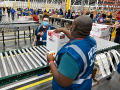 The first box containing the Johnson & Johnson COVID-19 vaccine heads down the conveyor to an awaiting transport truck at the McKesson facility in Shepherdsville, Ky., Monday, March 1, 2021. (AP Photo/Timothy D. Easley, Pool)