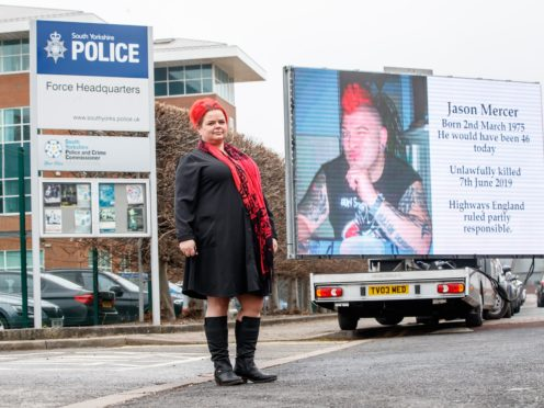 Claire Mercer in front of a sign bearing the image of her late husband Jason (Danny Lawson/PA)