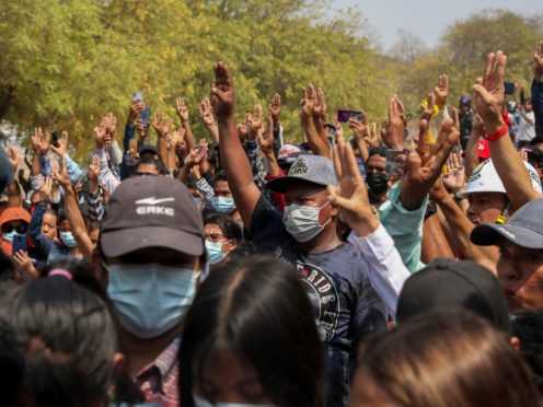 People flash a three-finger sign or resistance during the burial of anti-coup protester Kyal Sin in Mandalay, Myanmar, Thursday, March 4, 2021. Kyal Sin was shot in the head by Myanmar security forces during an anti-coup protest rally she was attending Wednesday. (AP Photo)