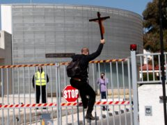 A protestor holding a cross climbs a gate outside Cyprus's national broadcasting building (AP/Petros Karadjias)