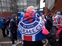 A Rangers fan wears a Steven Gerrard mask outside Ibrox (Robert Perry/PA)