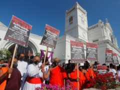 Cardinal Malcolm Ranjith, Archbishop of Colombo, 2nd left, along with Buddhist monks and other Catholic devotees hold placards during a protest demanding justice for the 2019 Easter Sunday bomb attack victims outside St Anthony's Church, one of attack sites, in Colombo (Eranga Jayawardena/AP)