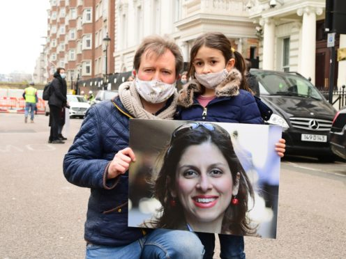 Richard Ratcliffe, the husband of Nazanin Zaghari-Ratcliffe, with his daughter Gabriella, during a protest outside the Iranian Embassy in London (Ian West/PA)