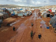 Syrian refugees walk through a camp for displaced muddied by recent rains near the village of Kafr Aruq, in Idlib province, Syria (Ghaith Alsayed/AP)