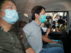 Ted Hui, centre, after he was arrested by police officers in Hong Kong (Kin Cheung/AP)