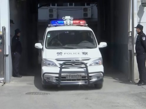 A police van leaves as part of a convoy of vehicles from a court building in Dandong in north-eastern China (AP)