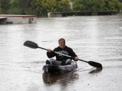 A man paddles through flood waters at Londonderry on the western outskirts of Sydney, Australia (Mark Baker/AP)