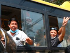 An arrested protester flashes the three-fingered salute while onboard a bus getting out of Insein prison (AP)