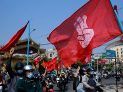 Engineers carry flags bearing the three-fingers salute during an anti-coup protest in Mandalay, Myanmar (AP)