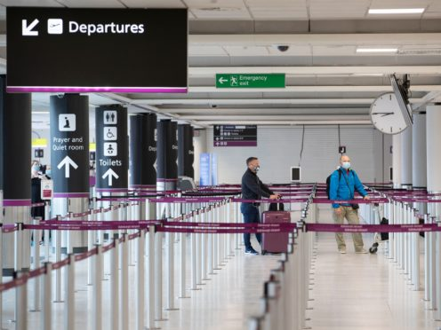 Passengers wearing a protective face masks at the Edinburgh Airport check-in area (Jane Barlow/PA)