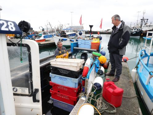 Agriculture Minister Edwin Poots (right) talks to fisherman Robert Oates (left) at Portavogie Harbour (Press Eye/PA)