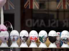 Face masks on display in a shop window (Andrew Matthews/PA)