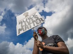 A woman holding a banner during in a Black Lives Matter protest rally at Woodhouse Moor in Leeds (Danny Lawson/PA)