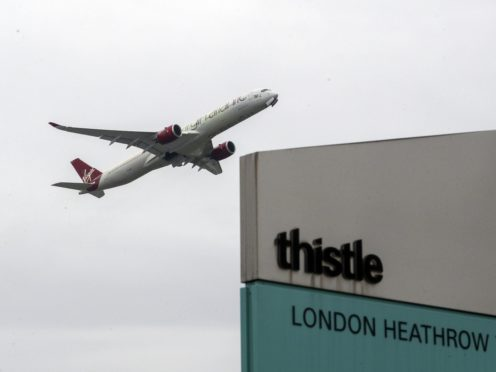 A plane passes over the Thistle Hotel at Heathrow (Steve Parsons/PA)