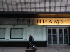 A person walks past closed doors and empty shop windows at the closed down Debenhams store on Oxford Street (Dominic Lipinski/PA)