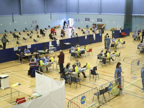 Members of the public receive a dose of the Covid-19 vaccine at the Cwmbran Stadium in south Wales (Geoff Caddick/PA)