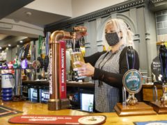 Melanie Scott pulling a pint at the Black Bull pub in Haworth, West Yorkshire (PA)