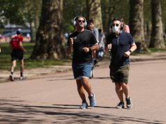 Joggers in Battersea Park, London (PA)
