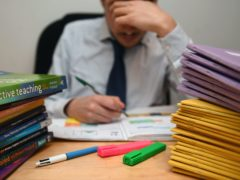 Undated file photo of school teacher looking stressed next to piles of classroom books. Nearly four in five teachers feel their job has adversely affected their mental health during the pandemic, a survey has suggested. Issue date: Saturday April 3, 2021.
