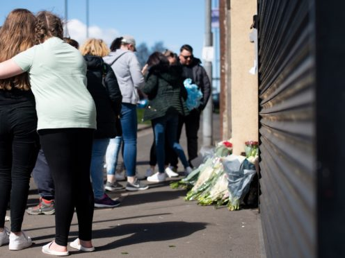 People embrace as flowers and tributes are left at the scene on High Street, Brownhills, near Walsall (Jacob King/PA)