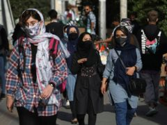 People wear protective face masks to help prevent the spread of coronavirus (Vahid Salemi/AP)
