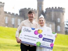 Sara Thomas with her partner Sean Warner, celebrating after she won on a National Lottery Scratchcard (Camelot)