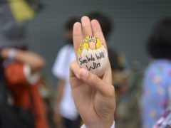 An anti-coup protester raises a decorated Easter egg along with the three-fingered symbol of resistance during a protest against the military coup (AP)