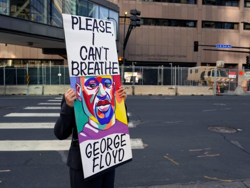 A protester holds a sign across the street from National Guard soldiers guarding the Hennepin County Government Centre, the trial venue (Jim Mone/AP)