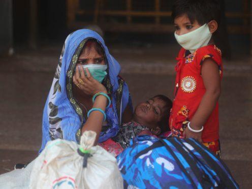 A woman and her children wait for a train at Lokmanya Tilak Terminus in Mumbai, India (Rafiq Maqbool/AP)