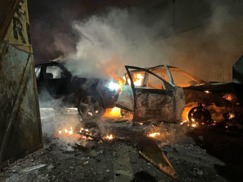 Cars have been set alight during another night of trouble in Belfast, including these which people from the loyalist side tried to drive through the Peace Gates in Lanark Way (Liam McBurney/PA)