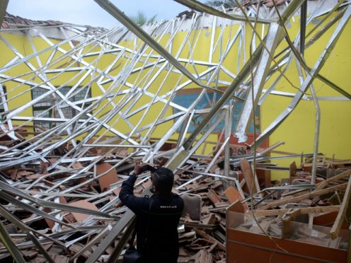 A local journalist films the damage to a classroom at a school following an earthquake in Malang, East Java, Indonesia (Hendra Permana/AP)