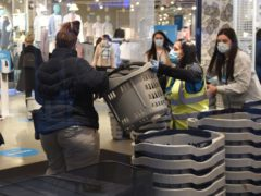 Early morning shoppers take a basket from a member of staff as they enter the Primark store in Birmingham (Jacob King/PA)