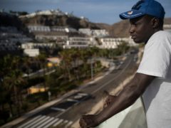 Senegalese migrant Fode Top looks at the view from the hotel room at Holiday Club Puerto Calma in Puerto Rico de Gran Canaria, Spain (Renata Brito/AP)