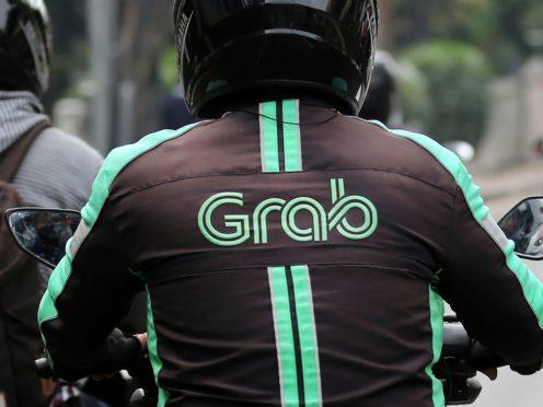 A GrabBike driver rides on his motorbike in Jakarta, Indonesia (Tatan Syuflana/AP)
