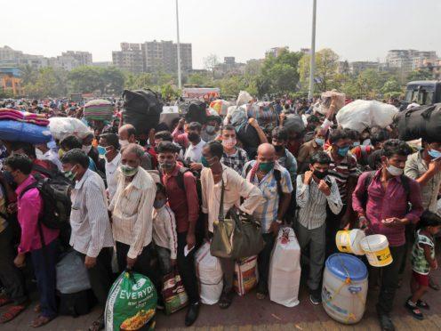 People wearing masks stand in queues to board trains at Lokmanya Tilak Terminus in Mumbai, India (Rafiq Maqbool/AP)