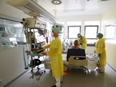 Medical personnel wearing protective equipment work in the intensive care ward for Covid-19 patients at the SRH Waldklinikum hospital in Gera, Germany (Bodo Schackow/AP)