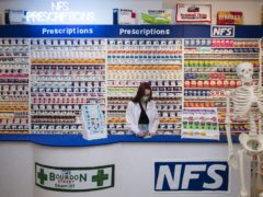 Gallery assistant Scarlett Taulbut behind the counter of artist Lucy Sparrow's NHS themed felt chemist art installation (Kirsty O'Connor/PA)