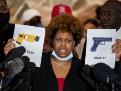 Naisha Wright, aunt of the deceased Daunte Wright, holds up images depicting X26P Taser and a Glock 17 handgun (John Minchillo/AP)