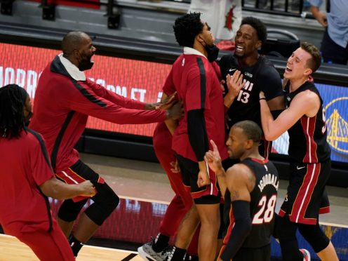 Miami Heat centre Bam Adebayo is mobbed by teammates after he made the winning shot against the Brooklyn Nets (Wilfredo Lee/AP)