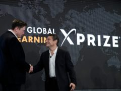 Elon Musk, left, shakes hands with XPRIZE founder and Executive Chairman Peter Diamandis during the presentation of the XPRIZE for Children's Literacy in Los Angeles, in this Wednesday, May 15, 2019, file photo. Organizers of a $20 million contest to develop products from greenhouse gas that flows from power plants announced two winners Monday, April 19, 2021, ahead of launching a similar but much bigger competition backed by Elon Musk. Both winners made concrete that trapped carbon dioxide, keeping it out of the atmosphere, where it can contribute to climate change. Production of cement, concrete's key ingredient, accounts for 7% of global emissions of the greenhouse gas, said Marcius Extavour, XPRIZE vice president of climate and energy.(AP Photo/Marcio Jose Sanchez, File)